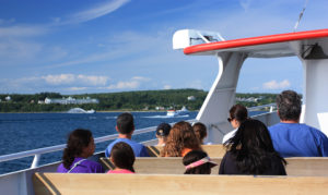 people riding the ferry to mackinac island on sunny day