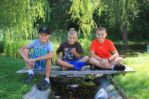 boys catching frogs at the pond
