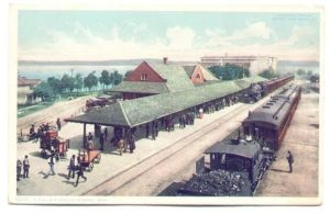 vintage postcard of train station with passengers waiting to board