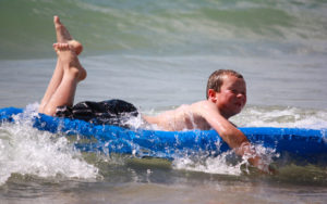 young boy riding the wave on raft in lake michigan