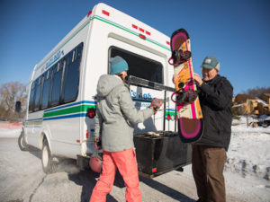 the nubs nob shuttle driver helping a snowboarder load her snowboard