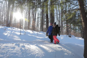 girls snowshoeing on the trails with the sun shining